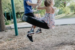 kids at the park on a tire swing